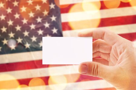 Male hand with blank business card and USA flag in background, mock up image, bokeh light effect Stock Photo