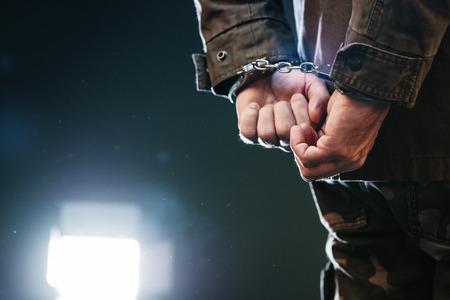cellule prison: soldat Menotté, officier de l'armée des hommes arrêtés dans la cellule de la prison noire