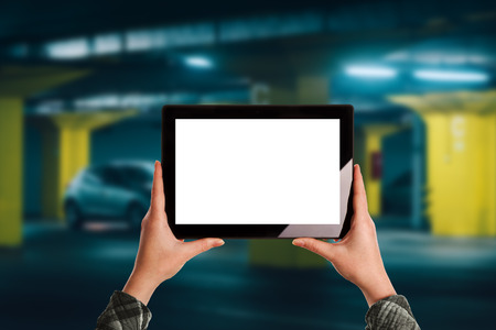 Woman using mobile application for car parking in underground garage, blank digital tablet screen as copy space for mock up design