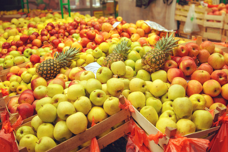 sorts: Crates with various sorts of apple and pineapple fruit on farmers market Stock Photo