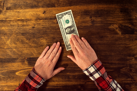minimum wage: Female hands and one dollar tip, cafe bar table top view Stock Photo