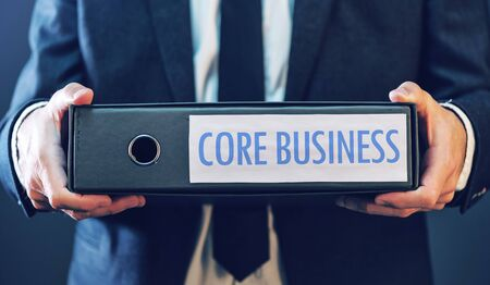 focuses: Core business with businessman and document ring binder, primary area or activity that company focuses on in its operations. Stock Photo