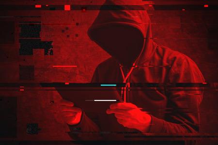 タブレット コンピューター、デジタル グリッチの効果を使用して認識できないフード付きハッカーとサイバー攻撃 写真素材