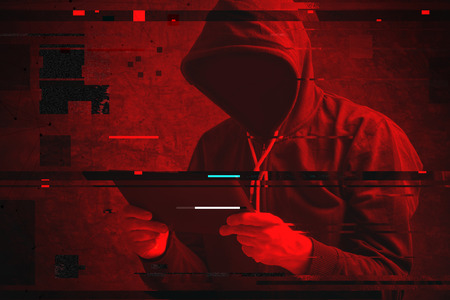 Cyber attack with unrecognizable hooded hacker using tablet computer, digital glitch effect Reklamní fotografie - 68924962