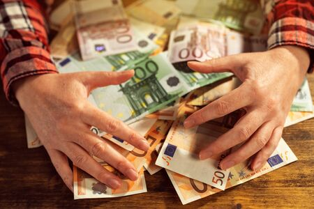 greedy: Greedy hands withdrawing pile of euro banknotes cash money on office desk