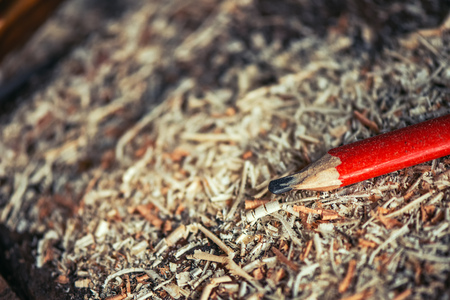 Red pencil on carpenters workshop table covered with wooden sawdust and scobs, macro with selective focus