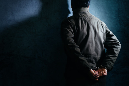 facing a wall: Arrested male criminal with handcuffs facing prison wall as copy space Stock Photo