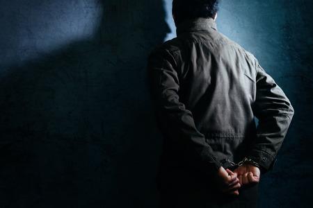 delincuencia: penal masculina detenidos con esposas enfrentan pared de la prisión como espacio de copia Foto de archivo