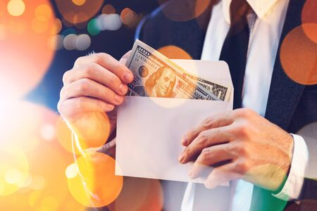 bribery: Bribery and corruption concept in business and politics with caucasian businessman taking cash money from envelope on city street at night