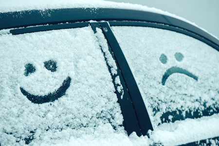 smiley face car: Happy and sad smiley emoticon face in snow on car windows, winter season joy and happiness concept