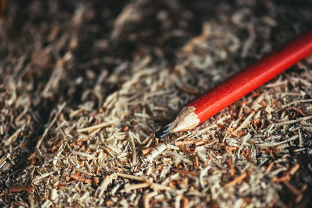 carpenter's sawdust: Red pencil on carpenters workshop table covered with wooden sawdust and scobs, macro with selective focus