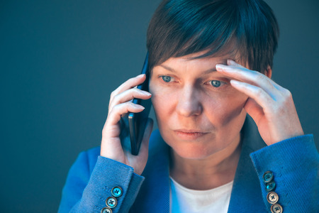 mobile telephone: Nervous worried businesswoman during unpleasant telephone conversation with mobile phone