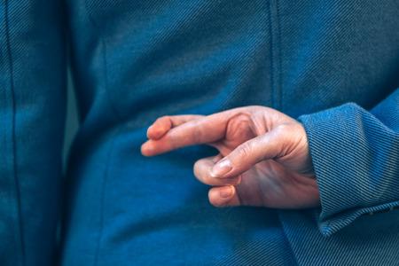 우아한 파란색 정장에서 여성 정치인 사람들이 거짓말을 할 때 손 제스처의 형태로 그녀의 뒤에 손가락을 넘어있다