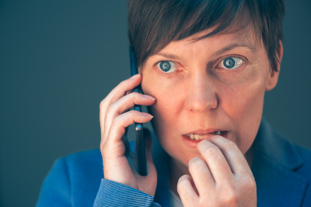 mobile telephone: Nervous businesswoman bites fingernails during telephone conversation on mobile phone Stock Photo