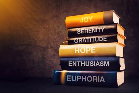 기쁨, 평온함, 감사, 희망, 열정 및 행복감 - 도서관 선반에 책 제목이있는 긍정적 인 감정과 감정 개념 스톡 콘텐츠