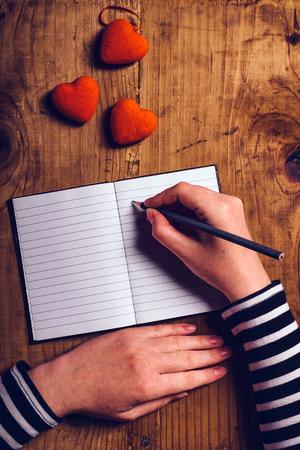 donna innamorata: Donna scrittura della carta della lettera di amore per San Valentino, vista dall'alto di mani femminili, retro tonica