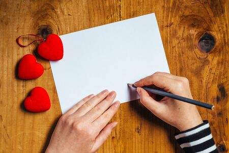 donna innamorata: Donna che scrive lettera d'amore o una poesia romantica per San Valentino, vista dall'alto Archivio Fotografico