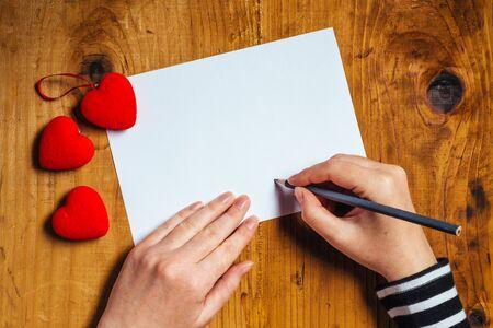 love letter: Mujer que escribe la carta de amor o un poema romántico para el día de San Valentín, vista desde arriba Foto de archivo
