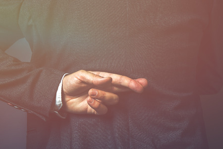 Dishonest politician telling lies, lying government representative holding fingers crossed behind his back
