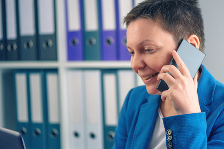 mobile telephone: Businesswoman during telephone conversation with mobile phone in office, looking at laptop computer screen Stock Photo