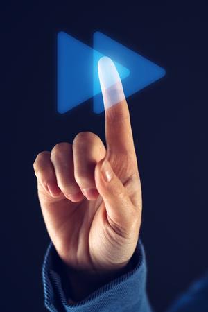 Businesswoman pushing fast forward button on virtual screen