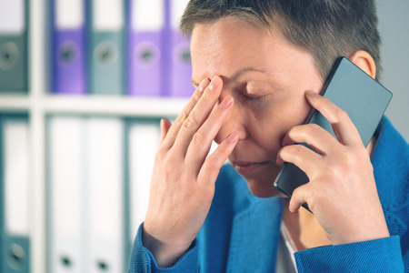 forgetful: Forgetful businesswoman during mobile phone conversation, caucasian business female just realized that she forgot something Stock Photo