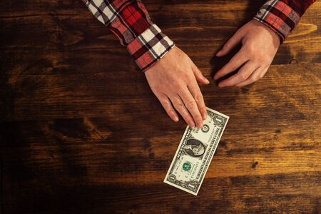 one female: Female hands and one dollar tip, cafe bar table top view Stock Photo