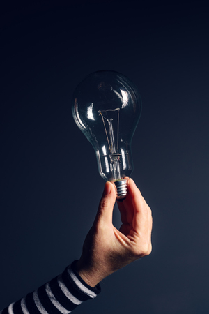 creativity symbol: Female hand offering light bulb, the symbol of new ideas and creativity