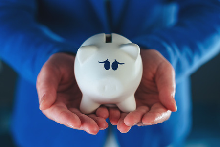 coin bank: Sad piggy coin bank in businesswomans hands, desperate look on face