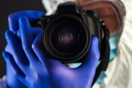 Crime scene forensics investigator with digital camera taking pictures as evidence for the investigation Stock Photo
