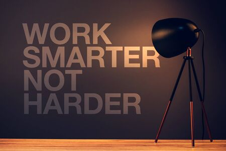 harder: Work smarter not harder, motivational quote on office wall illuminated with desk lamp