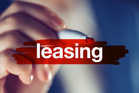 Leasing, business concept - businesswoman highlighting word with red marker pen Stock Photo