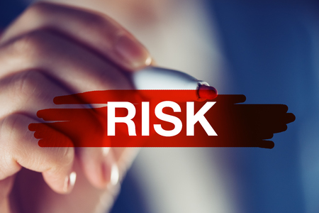 Risk in business concept, businesswoman marking the word with red highlighting marker pen