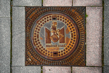 MALMO, SWEDEN - MARCH 07, 2017: Malmo Stad manhole cover with Coat of arms, crowned griffin head is Malmos municipal arms since 1437th
