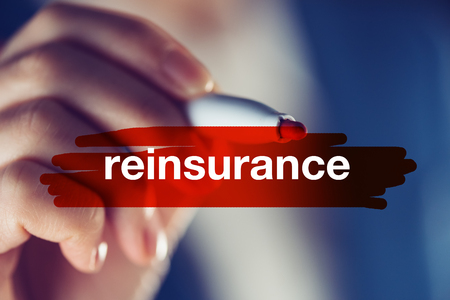 Reinsurance business concept, businesswoman highlighting word with red marker pen Stock Photo