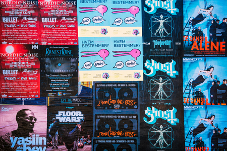 increasingly: COPENHAGEN, DENMARK - MARCH 11, 2017: Posters for various music concert in Copenhagen, Denmark. Danish capital flourishing scenes increasingly attracts visitors.