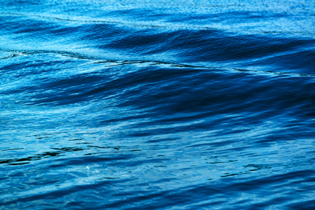 ocean background: Sea waves formed from sailing ship, abstract dark blue background