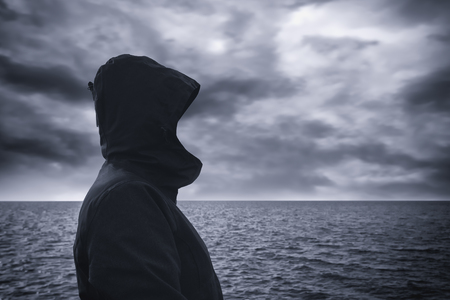 anticipating: Faceless hooded person looking into distance at horizon over the sea water on cold windy winter day, anticipating unpredictable future