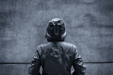 insurmountable: Unrecognizable hooded female person facing concrete wall as insurmountable obstacle, young adult woman in urban surrounding confronting problems and difficulties in life. Stock Photo