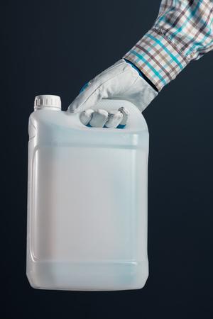 Granjero macho irreconocible con contenedor de plástico sin marcar que contiene pesticidas para el procesamiento de plantas en la agricultura Foto de archivo - 76271464