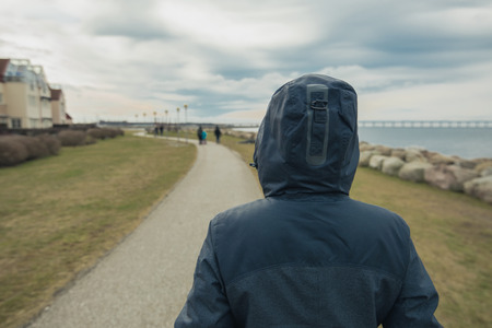 aloneness: Lonely hooded female person from behind standing at seashore and looking into distance on a cold winter day, concept of waiting, anticipation, hope and expectancy Stock Photo