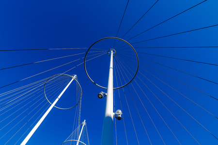 Abstract architecture, metallic posts with strings against blue sky, unusual low angle view