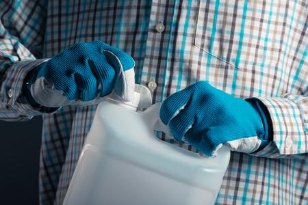 Granjero macho irreconocible con contenedor de plástico sin marcar que contiene pesticidas para el procesamiento de plantas en la agricultura Foto de archivo - 75811439