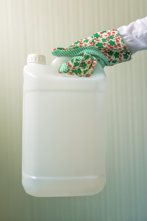 unlabeled: White unlabeled plastic 5 liters tank canister in female hand, chemistry and chemical liquids mock-up container