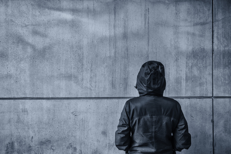 Unrecognizable hooded female person facing concrete wall as insurmountable obstacle, young adult woman in urban surrounding confronting problems and difficulties in life. Stock Photo