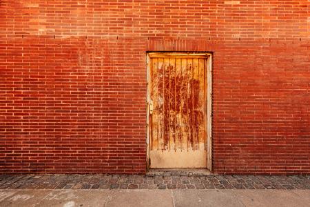backdoor: Backdoor, old weathered door and brick wall, backstreet urban detail
