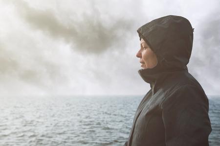 unpredictable: Optimistic female person enjoying morning sunlight at sea coastline on cold windy winter day, anticipating unpredictable future Stock Photo