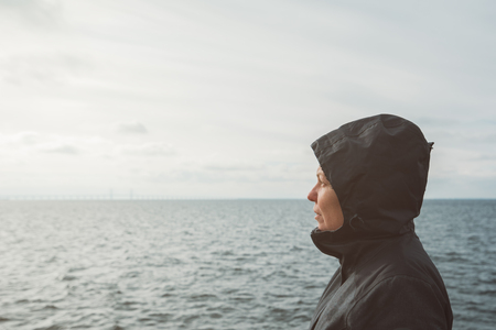 anticipating: Optimistic female person enjoying morning sunlight at sea coastline on cold windy winter day, anticipating unpredictable future Stock Photo