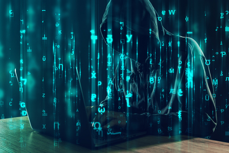 Hooded unrecognizable hacker and cyber criminal working on laptop, programming bugs and viruses for computers, matrix like code is overlaying image
