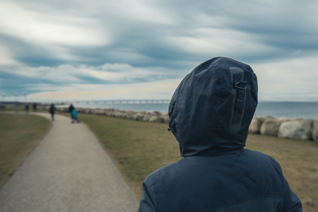 expectancy: Lonely hooded female person from behind standing at seashore and looking into distance on a cold winter day, concept of waiting, anticipation, hope and expectancy Stock Photo